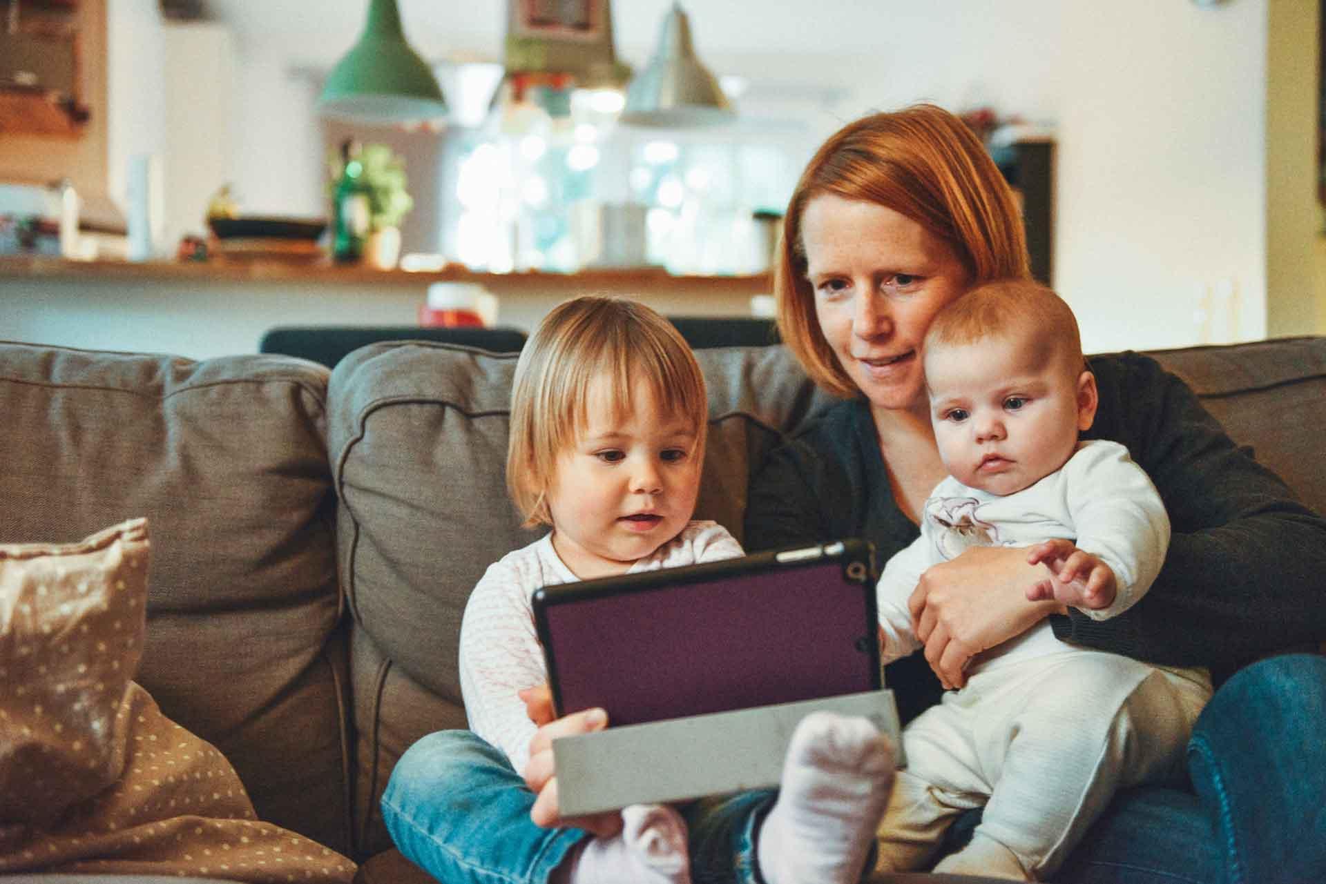 Generation Alpha Jahrgang - Familie mit Baby und Kleinkind am Tablet